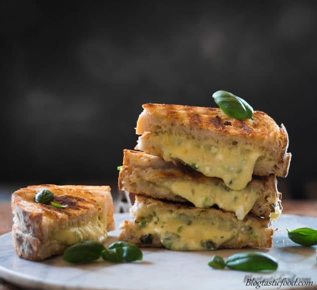 grilled cheese sandwiches stacked on top of one another with the cheese oozing out.