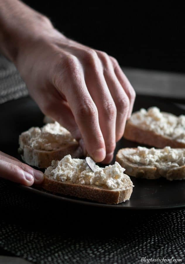 Fresh ricotta cheese being spread over small slices of toast.