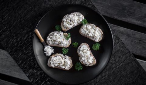 An overhead photo of ricotta cheese on small pieces of toast.