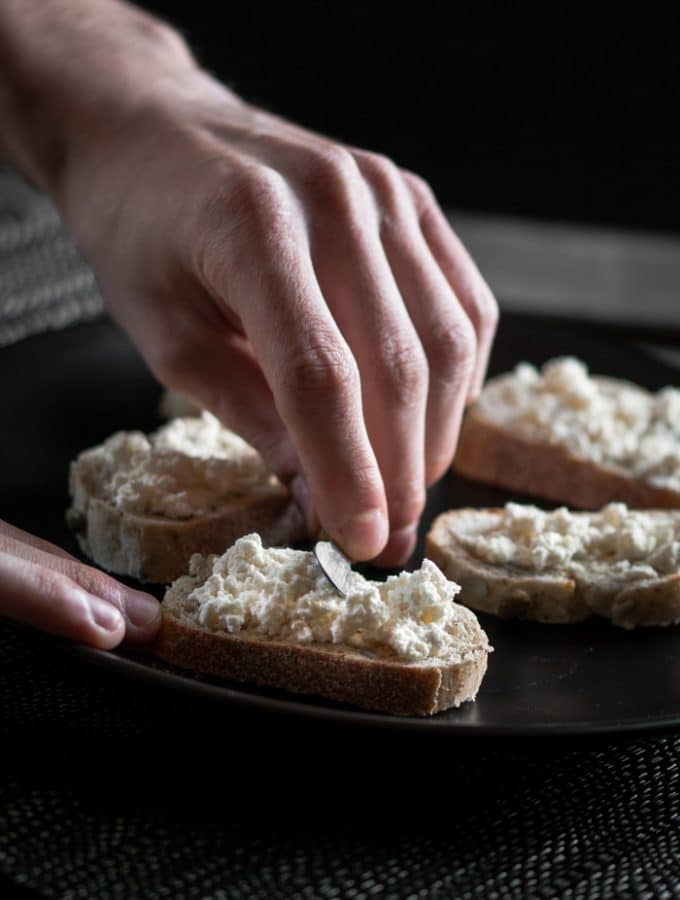 A photo of ricotta cheese being spread over