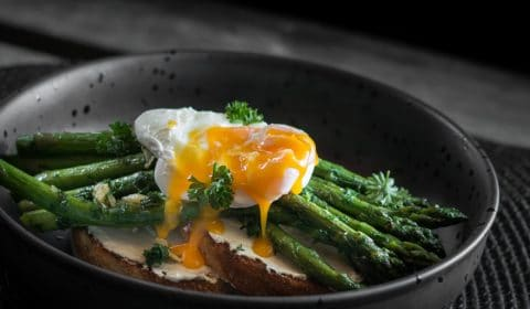 A photo of a poached egg with the yolk broken over asparagus and toast.