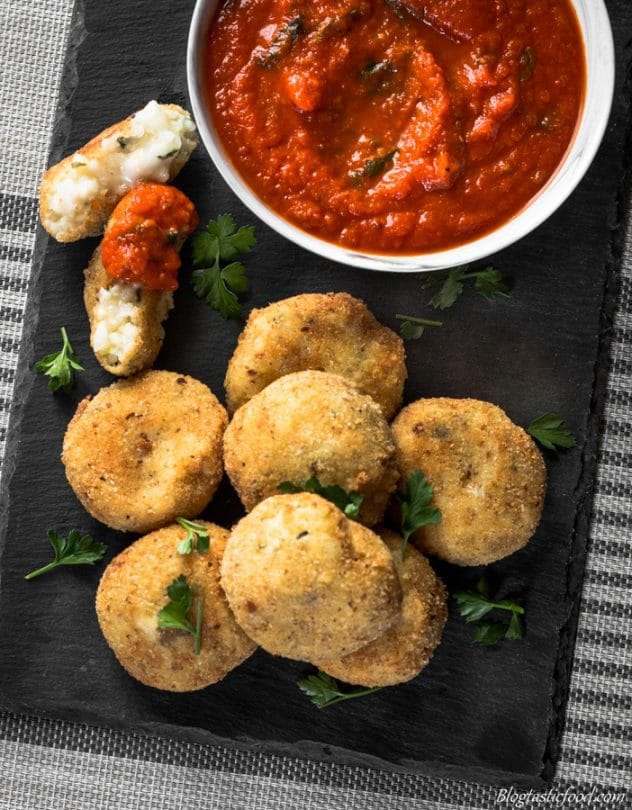 An overhead photo of arancini balls and a bowl of red pepper and tomato dipping sauce served on a sushi platter.
