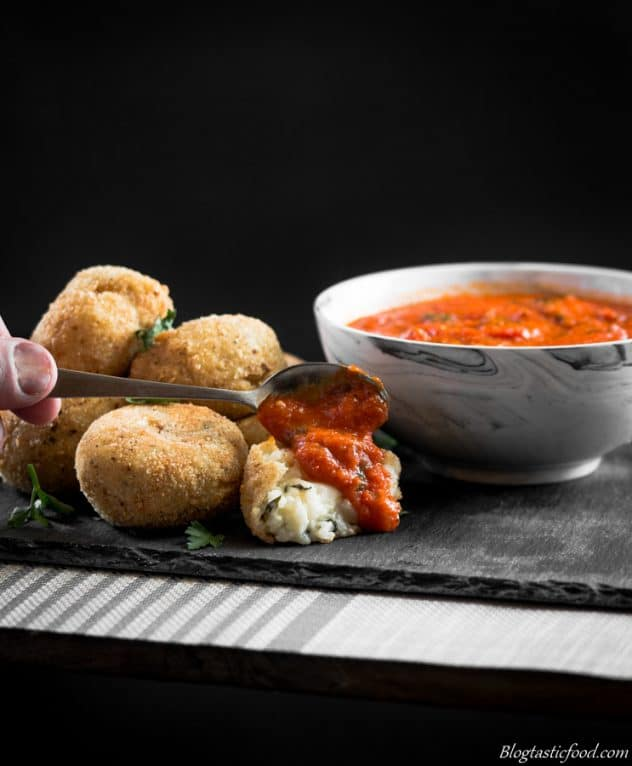 A photo of some spoonong red pepper and tomato dipping suace over arancini balls.
