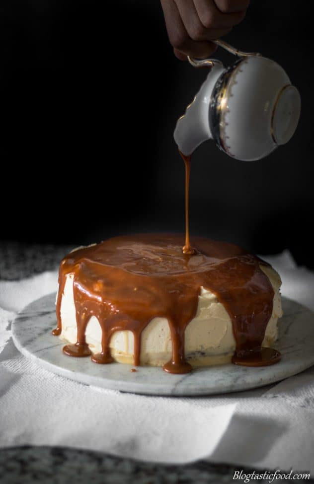A photo of someone pouring caramel over a baileys frosted cake.