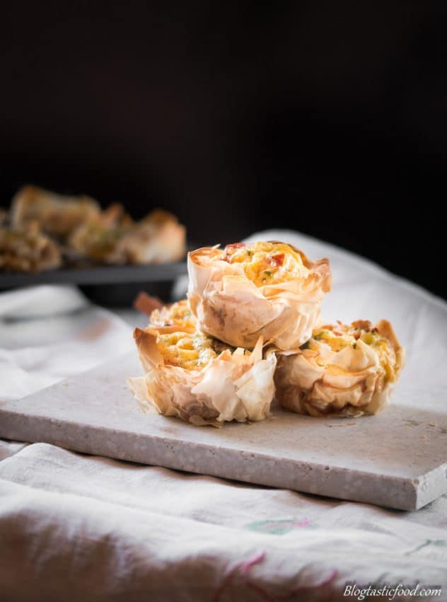 A photo of filo pastry filled mini quiches in a white slate.