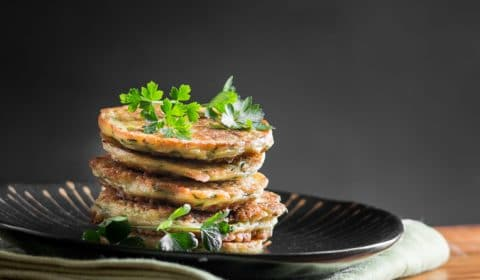 A group of zucchini fritters stacked on top of each other.