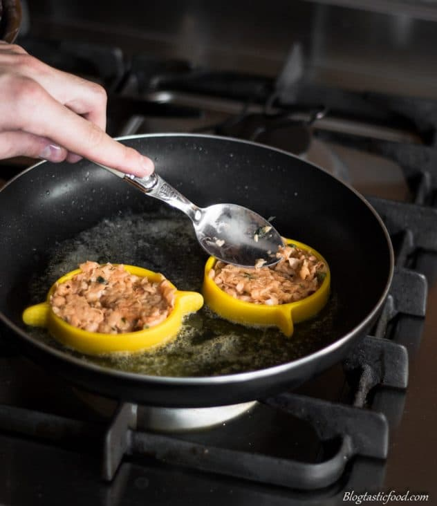 A photo of someone using an egg ring to fry hash browns in a non-stick pan.