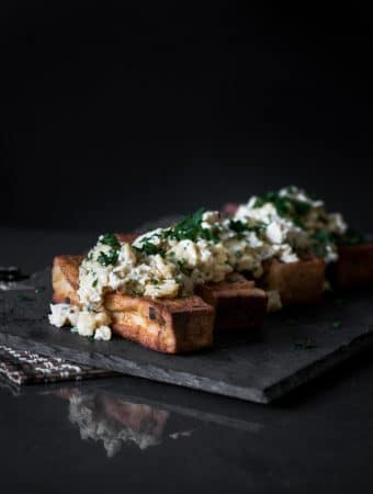 A dark, moody photo of French toast with scrambled eggs served on top.