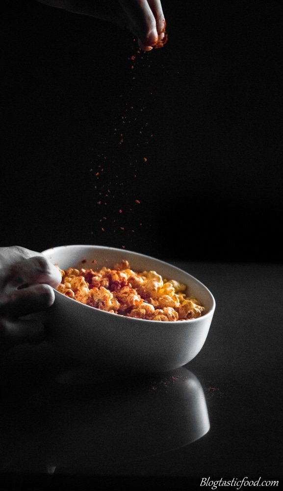 Someone sprinkling sweet paprika in a bowl filled with popcorn.