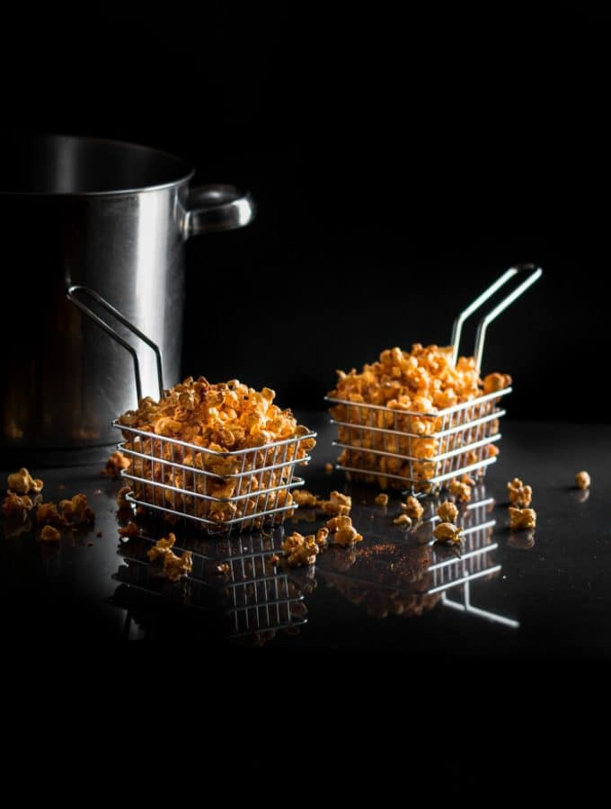 A dark. moody photo of savory spiced popcorn in metal baskets.