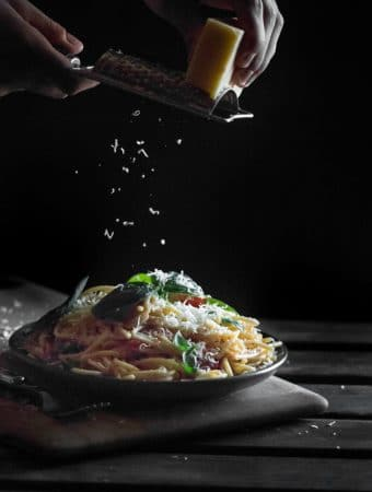 Parmesan cheese being grated over spaghetti.