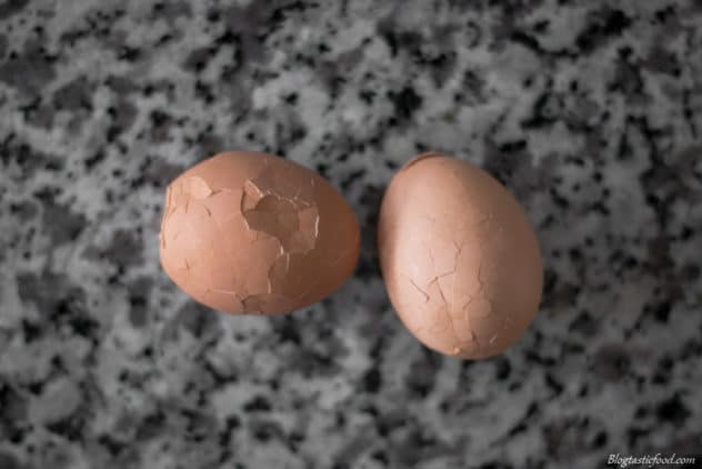 A photo of 2 boiled eggs where the shell has been cracked all over.