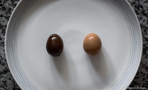 A photo showing the difference between an egg marinated in dark soy sauce and an egg marinated in light soy sauce.