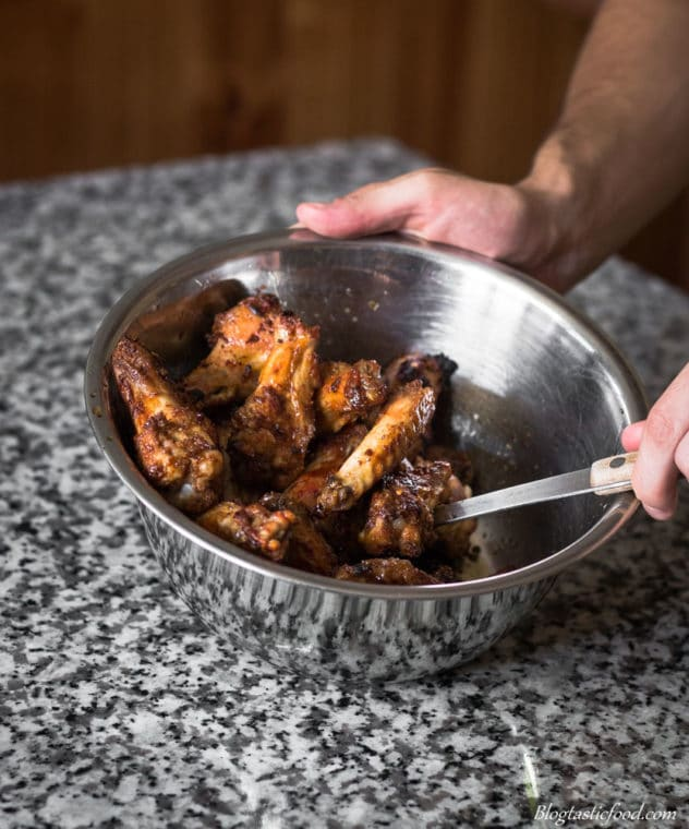 A photo of cooked chicken wings getting coated in honey soy mustard glaze.