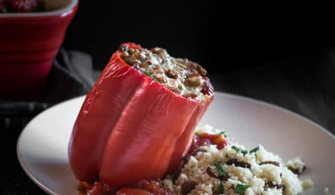 A turkey and lentil stuffed red bell peppers with melted cheese on top, served with couscous.