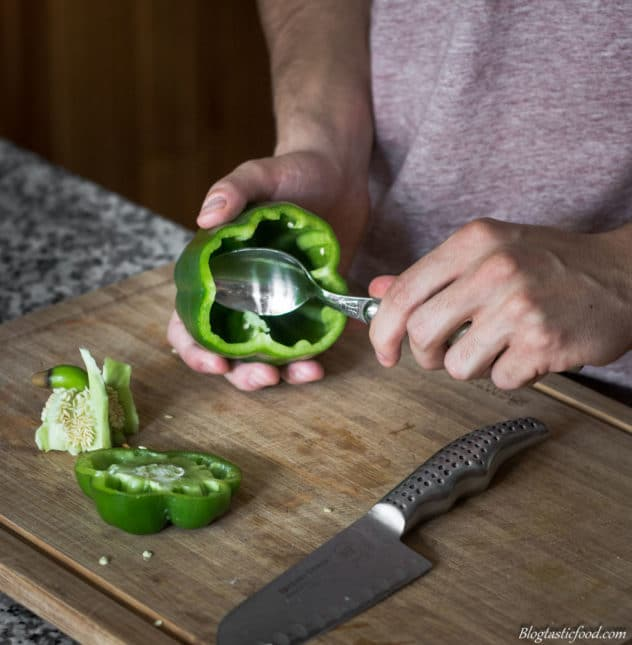 A photo of someone scooping the seeds out of a hollowed bell pepper.