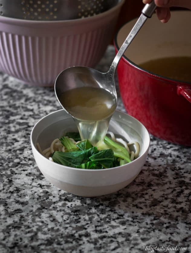 A photo of me ladling broth over udon noodles and bok choy in a bowl.