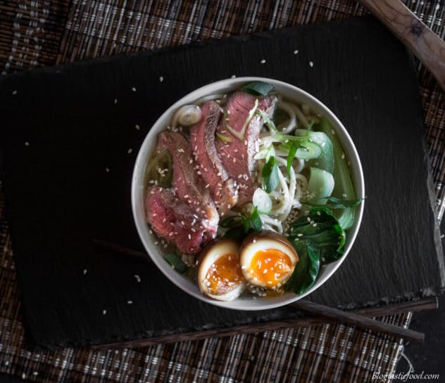 An overhead photo of beef and udon noodle soup with a ramen egg.