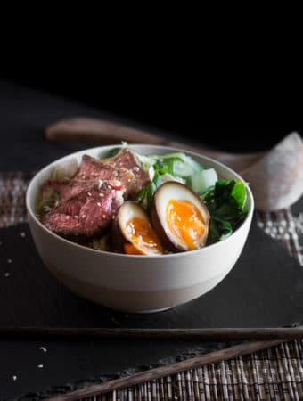 Slices of medium rare beef, udon noodles, bok choy and broth served in a bowl.