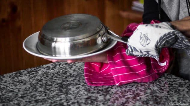 A photo of someone flipping a tart tatin onto a plate.