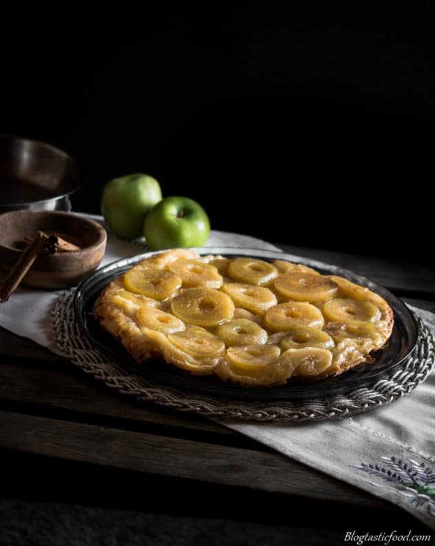 A photo of a tarte tatin on a dark glass plate.