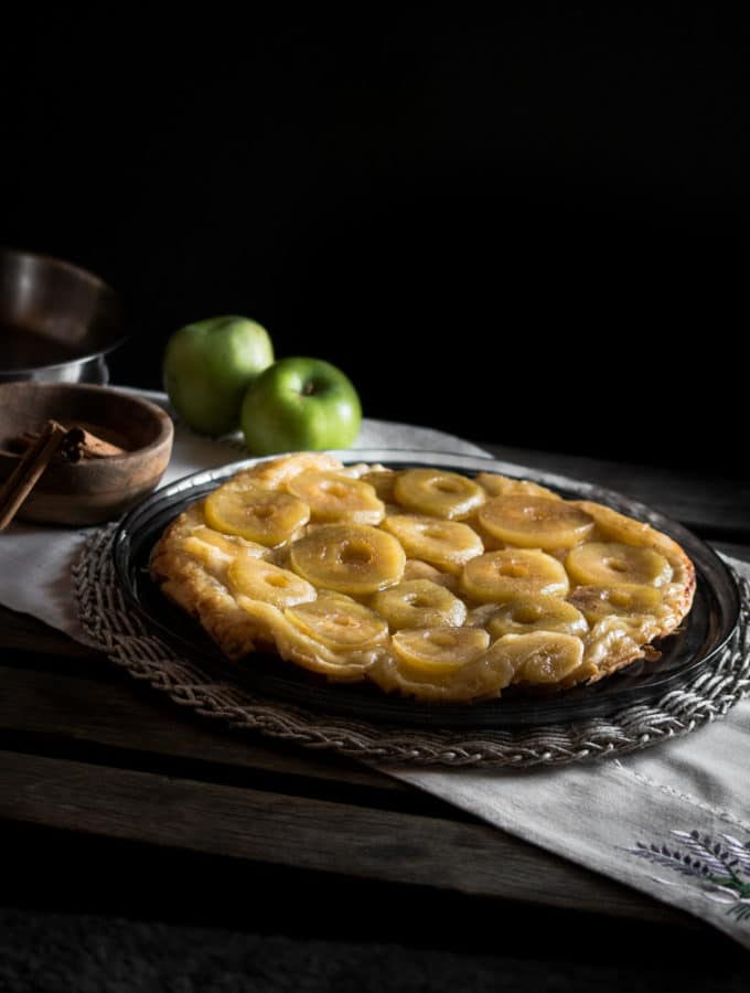 A photo of a tarte tatin with apples and cinnamon cloves in the background.