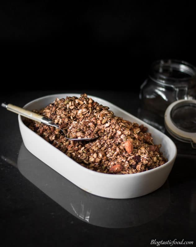 A photo of toasted chocolate Granola in a tile tray a spoon in it.
