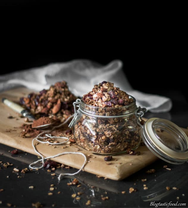 A photo of toasted healthy chocolate granola on a board, served in a glass jar.