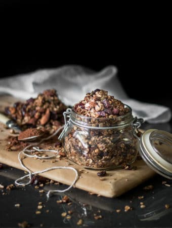A dark and moody photo og a glass jar filled with chocolate flavoured granola mix.