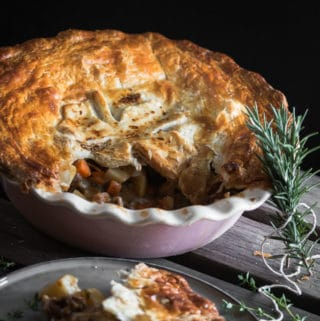 A photo of a Irish stew pie for St Patricks Day with herbs scattered around it.