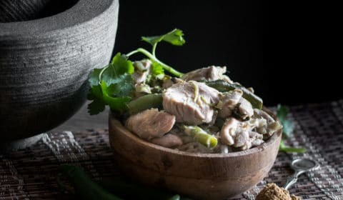 A photo of chicken green curry and rice served in a wooden bowl with a pestle mortar beside it.