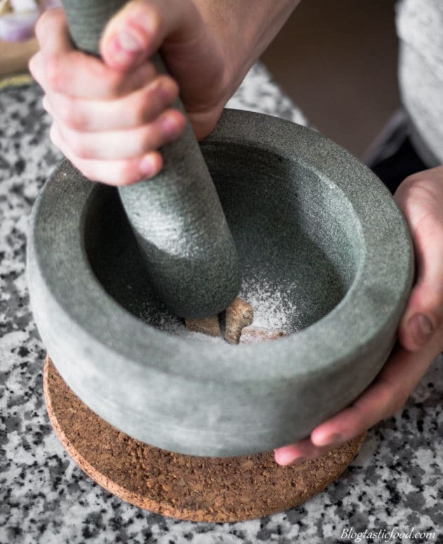 A photo of someone bashing salt and galangal together in a pestle mortar.