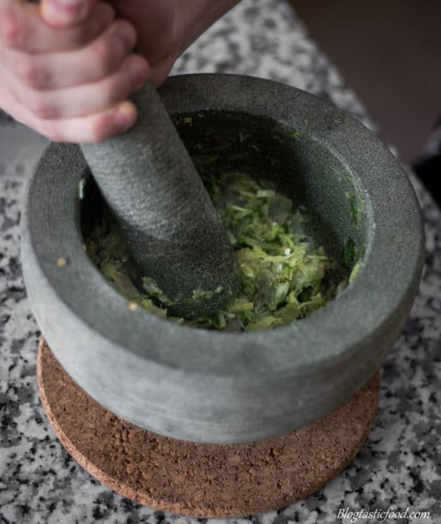 A photo of a bunch of aromatics getting bashed in a pestle mortar.