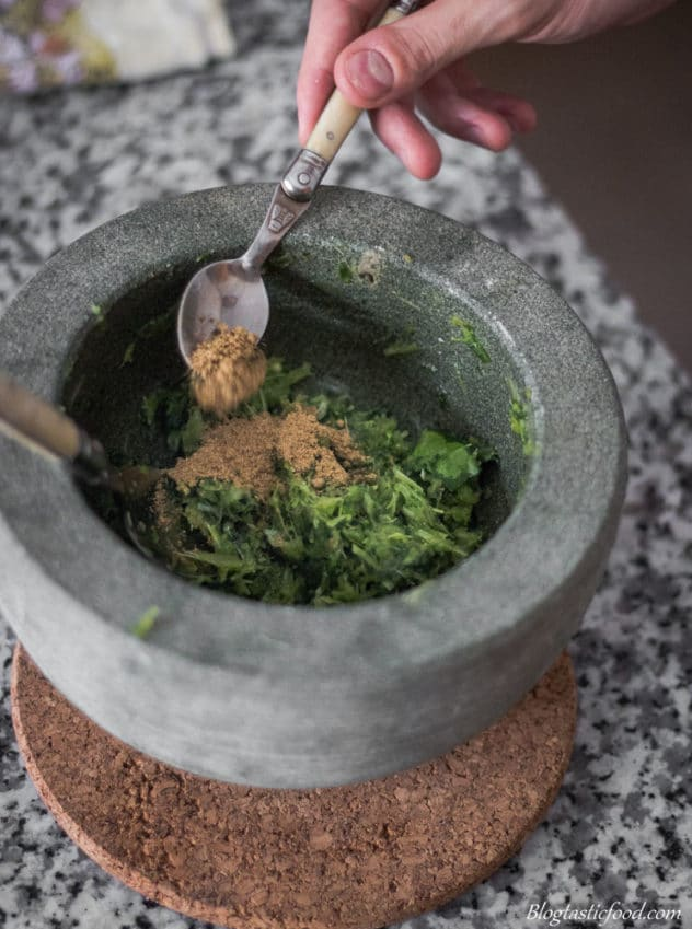 A photo of someone adding spices to a Thai green curry paste in a pestle mortar.