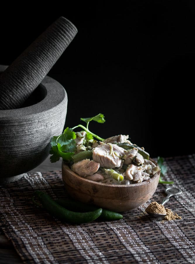 A dark, moody photo of green chicken curry served in a small bowl.