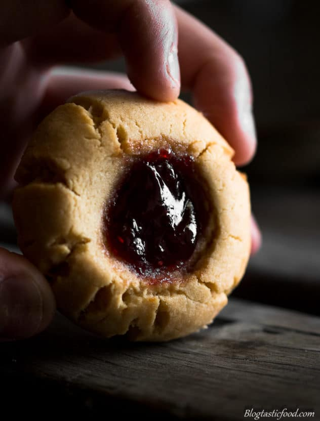 A close up photo of someone holding a peanut butter and jam cookie.