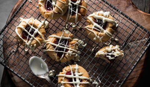 An overhead photo of white chocolate drizzle peanut butter and jam cookies on a cooling rack.