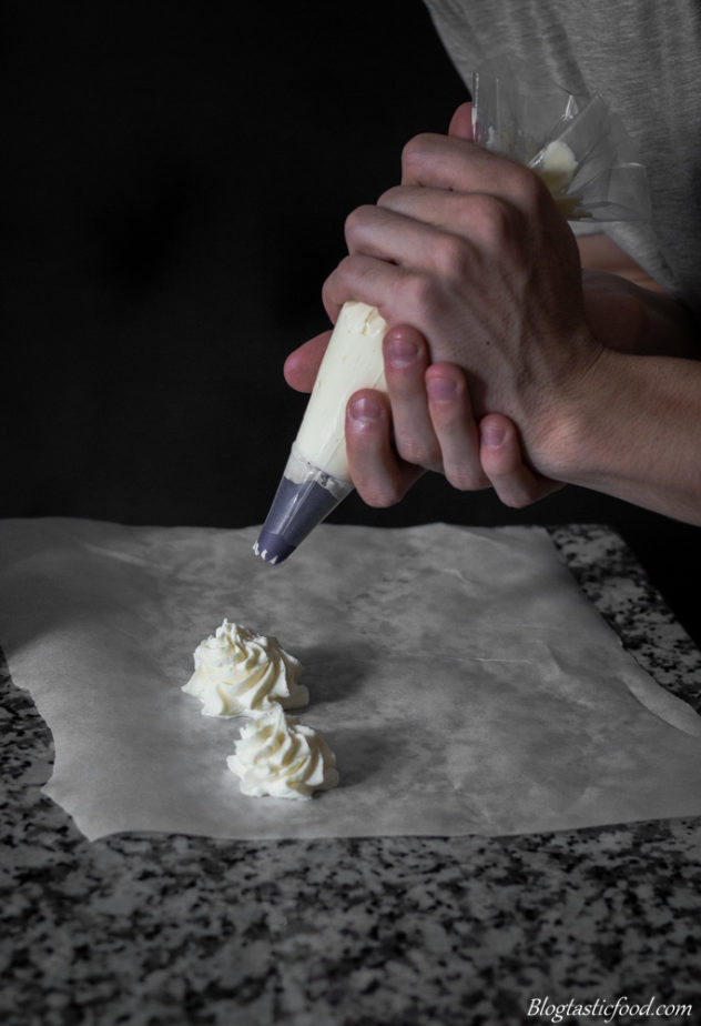 A photo of someone piping butter-cream on baking paper to practice.