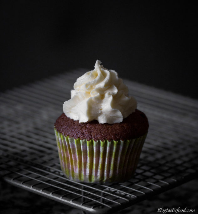 A photo of a cupcake on a cooling rack with butter-cream piped on top.