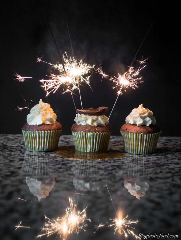 A photo of three cupcakes, one of them having three sparklers in it that have been lit up.