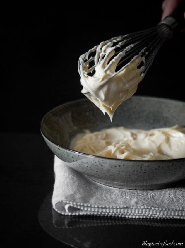An eye level photo of mayonnaise hanging off a whisk.