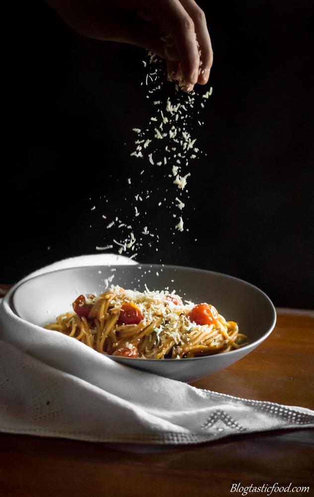Parmesan being Sprinkled over Pasta