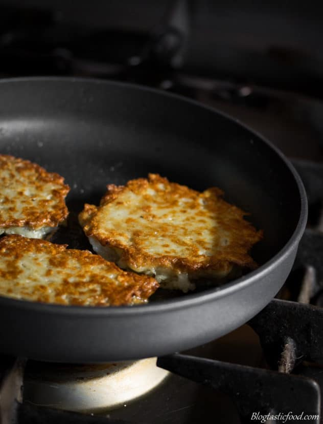 A close of photo of grated potato cakes frying in a pan.
