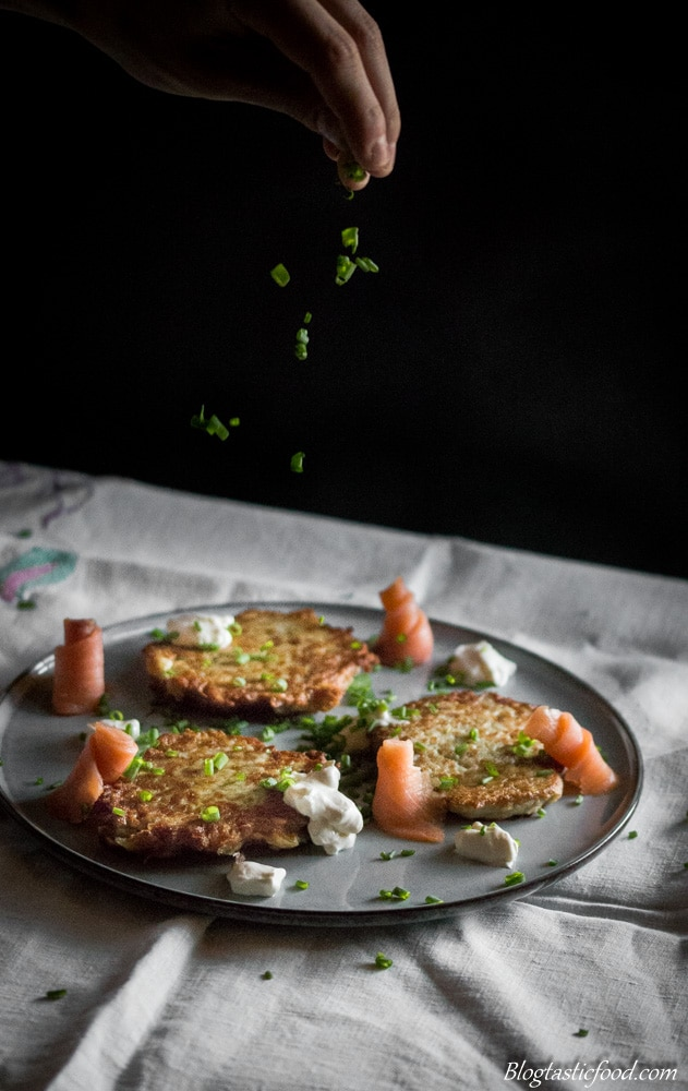A plate of smoked salmon, sour cream and potato cakes with chives being sprinkled on top