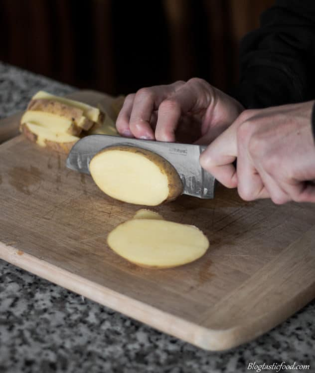 A photo of someone slicing a potato into disks.