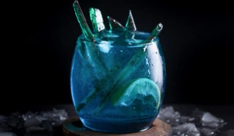 A photo of green shards of green candy sticking out of a white walker themed cocktail, served on a coaster.