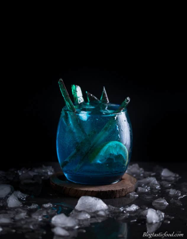 An eye level photo of a blue cocktail with spikes of green candy sticking out of it. Surrounded my melting ice.