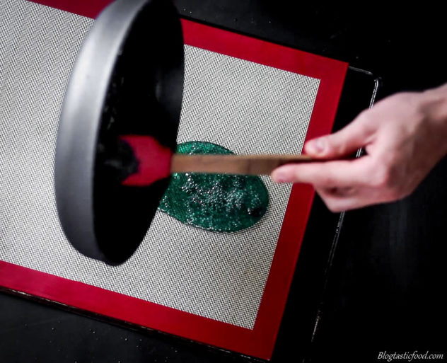 An overhead photo of green caramel being poured out onto a silicon mat.