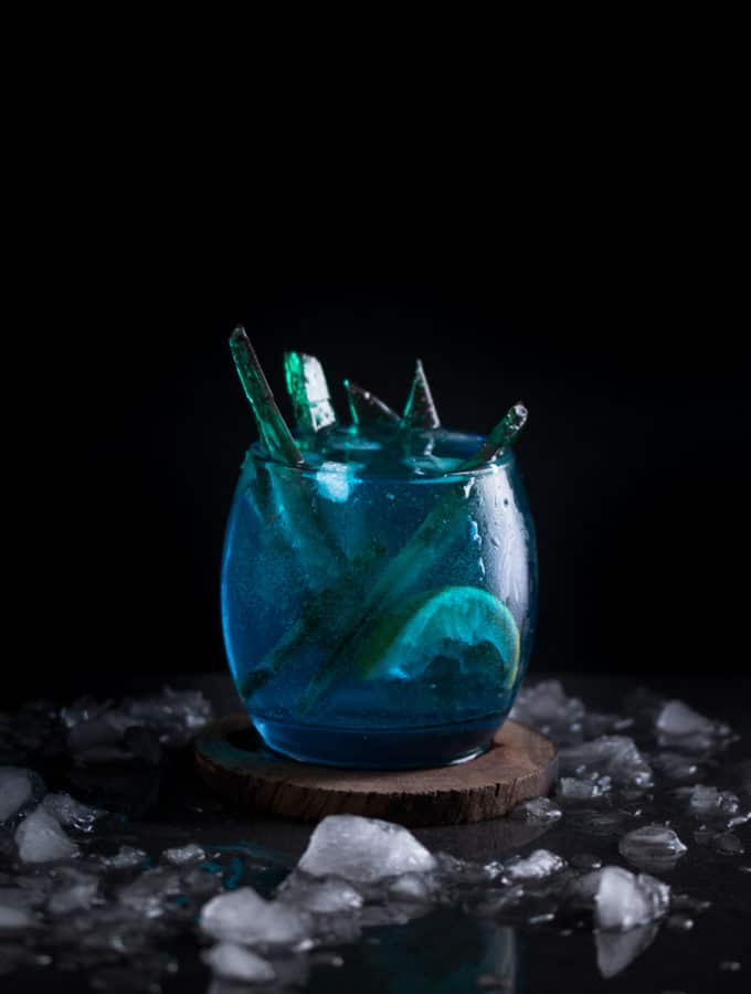 A photo of a blue white walker themed cocktail with green candy inside of it, served on a wooden coaster.