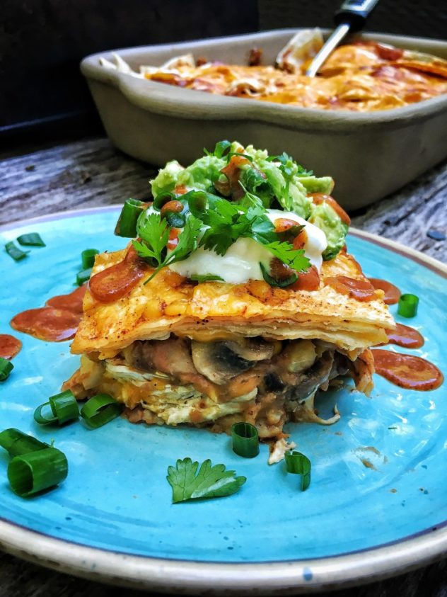 A photo of Mexican inspired lasagna served on a blue plate.
